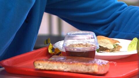 Un élève, dont on voit un bras, est assis devant un plateau d'aliments dans la cafétéria de son école.