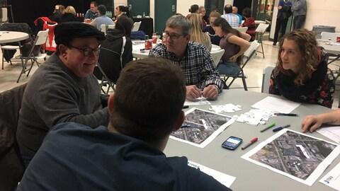 Des citoyens discutent autour d'une table.