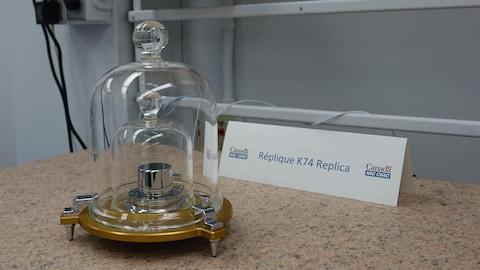 Un cylindre de platine et d'iridium sous deux cloches de verres.