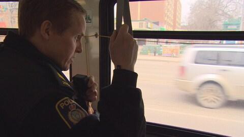 Un policier est debout dans un autobus en train de parler dans sa radio. Ses yeux sont fixés sur la route.