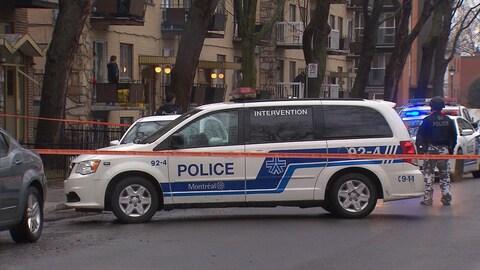 Un policier du groupe d'intervention à côté d'un véhicule de police