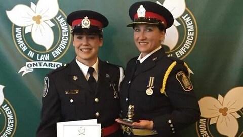 Deux policières posant avec un prix devant une bannière.