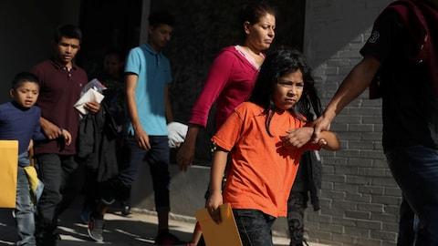 Des enfants accompagnés par des adultes à l'extérieur d'un bâtiment en briques.