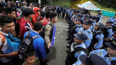 Des migrants se tenant devant des policiers.