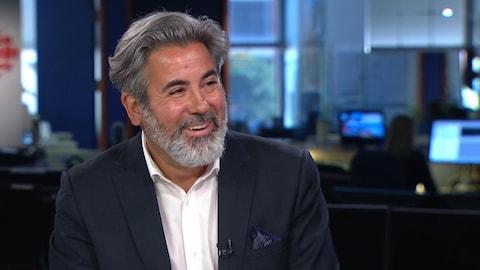 Un homme souriant sur un plateau de télévision.
