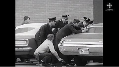 Policiers qui se cachent derrière une voiture, arme à la main.