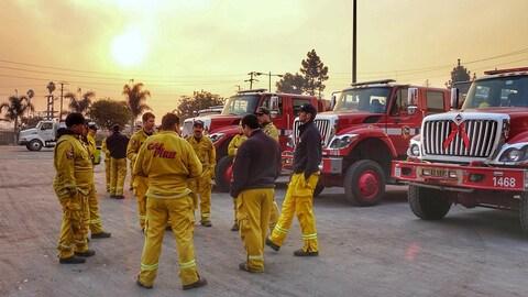 Un groupe de pompiers devant leurs camions