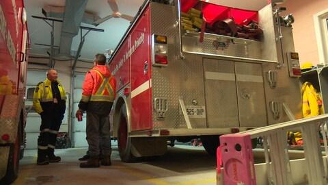Des pompiers discutent debout près de deux camions d'incendies.