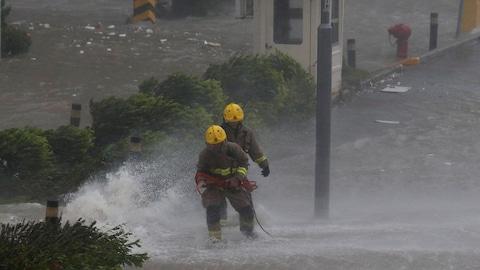 Des pompiers interviennent alors que de hautes vagues déferlent sur les rives de Heng Fa Chien, un quartier résidentiel de  Hong Kong.