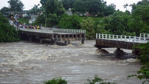 Un pont emporté par une rivière en crue.