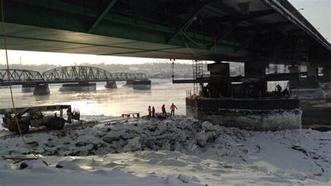 Des travailleurs s'affairent sous la structure du pont Dubuc.