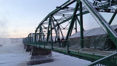 Des citoyens marchent sur le pont Sainte-Anne.