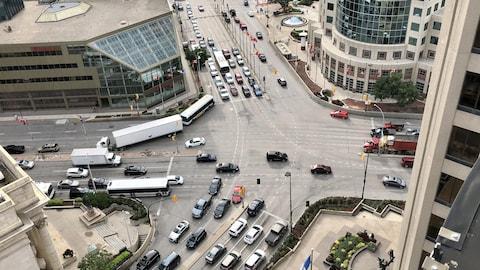 On voit de haut une intersection importante dans un centre-ville, avec des voitures et des camions qui circulent. On peut ausi voit qu'il n'y a pas d'endroits permettant aux piétons de traverser la rue sur cette intersection.