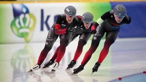 Isabelle Weidemann, Valérie Maltais et Ivanie Blondin pendant une compétition de patinage de vitesse sur longue piste.