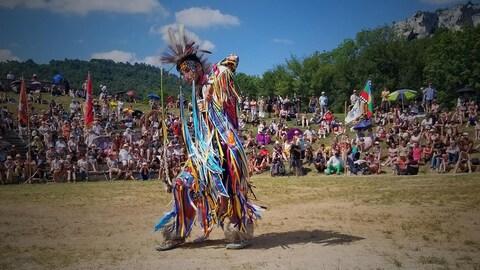 Sylvain Guay, vêtu d'un costume traditionnel autochtone, danse.