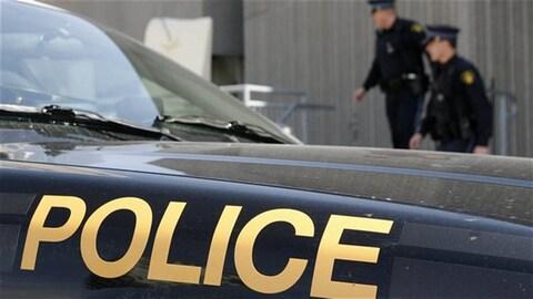 Une voiture de police avec des agents en arrière-plan.