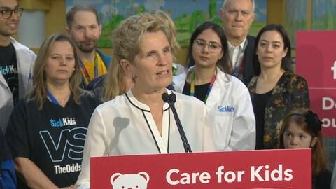 Photo de Kathleen Wynne portant une blouse blanche au podium.