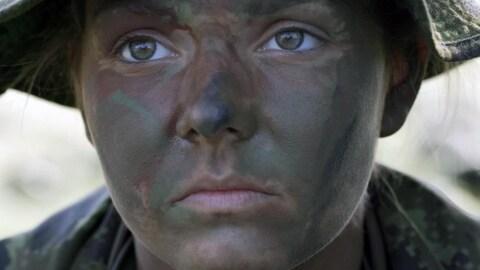 Une femme soldat, le visage maquillé de vert kaki, regarde droit devant elle.