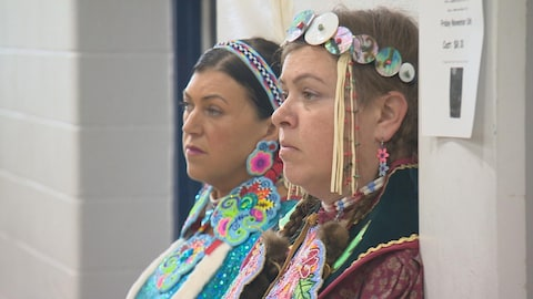 Gros plan des visages de deux femmes accotées sur le mur, vêtues traditionnellement..