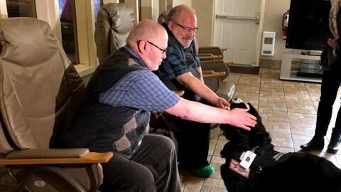 Deux hommes caressent la chienne Preti.