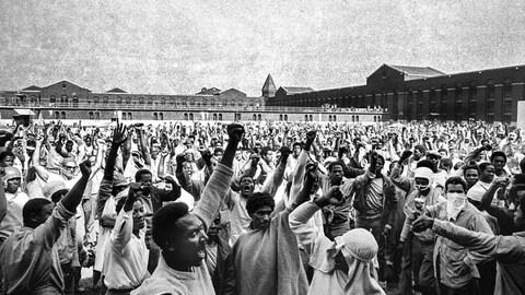 Plusieurs prisonniers lèvent le poing dans une cours de prison.
