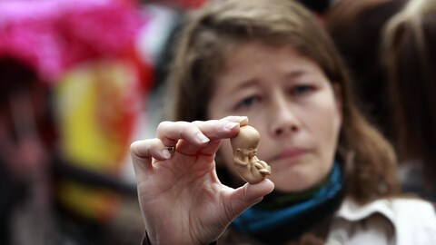 Une militante pro-vie présente un modèle d'embryon de 12 semaines lors d'une manifestation devant la clinique Marie Stopes, à Belfast.