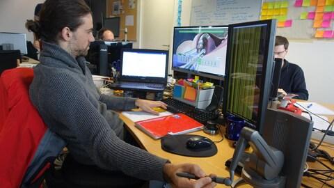 Un homme devant ses multiples écrans d'ordinateur,