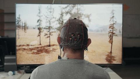 Une photo montrant un homme de dos. Il regarde la télévision et porte un chapeau ressemblant à un casque de bain troué auquel sont reliées des électrodes.