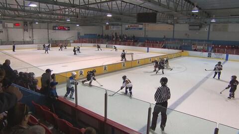 Un muret divise la glace d'une patinoire en deux, où de jeunes joueurs disputent une partie de hockey.