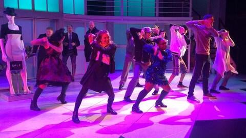 Des actrices et des acteurs dansent sur une scène dans leurs costumes.