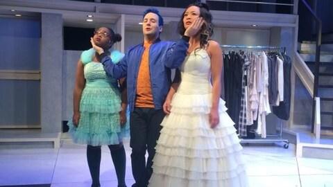 Trois comédiens, dont deux filles en robes de dentelle, répètent une scène.