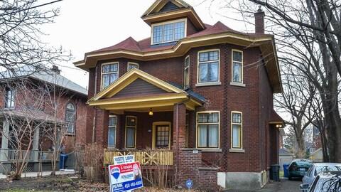 Une maison en briques avec une affiche à vendre de Remax.