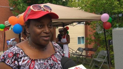Une femme portant une casquette des Sénateurs donne une entrevue devant un kiosque où l'on distribue de la soupe.