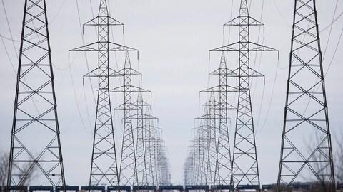 Des pylônes électriques à perte de vue sont allignés les uns après les autres