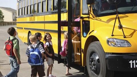 Des enfants montent dans un autobus scolaire