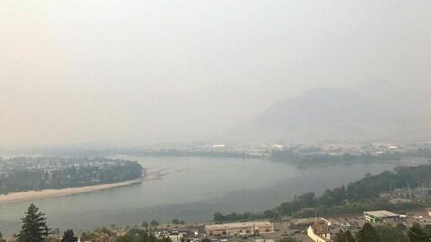 Une ville, une rivière et des montagnes sous un épais manteau de fumée