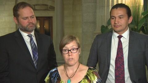 une femme entourée de deux hommes qui la regardent alors qu'elle parle.