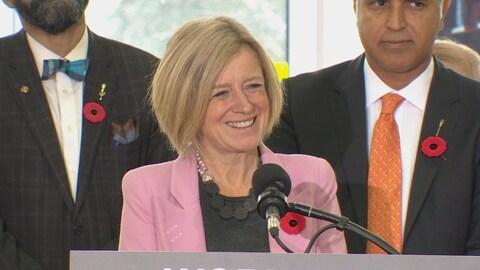 Rachel Notley sourit à la caméra. Elle porte un veston rose et un coquelicot du Jour du souvenir.