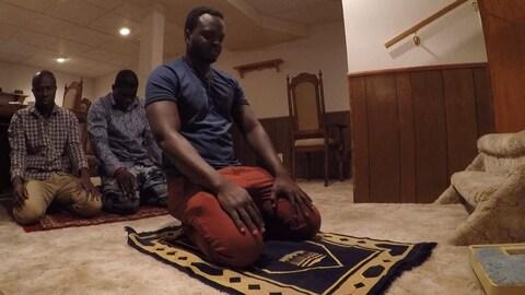 Trois hommes à genoux sur des tapis durant la prière.