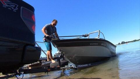 Un homme met son bateau à l'eau en se servant d'une rampe sur la rive.