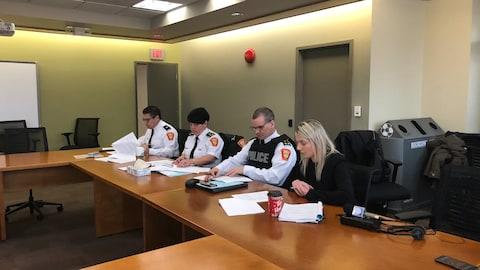 Holly Walbourne assise à une table en compagnie de trois représentants de la police de Thunder Bay, dont la chef, Sylvie Hauth.