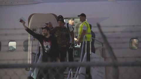 Des  hommes descendent d'un avion.