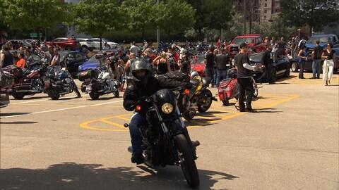 Un motard démarre devant une foule de personnes rassemblée avec leur moto