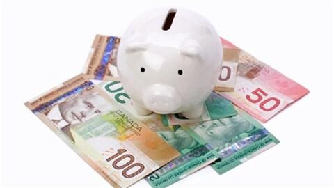 Une tirelire en forme de cochon posée sur des billets de banque