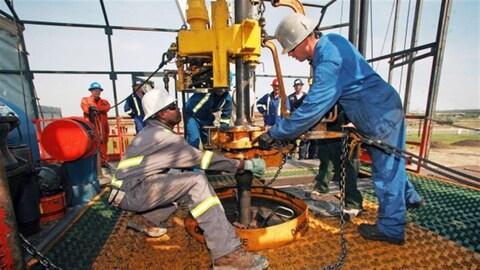 Des travailleurs sur le site d'un forage pétrolier.
