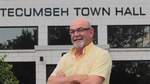 Portrait d'un homme en chemise jaune devant un bâtiment