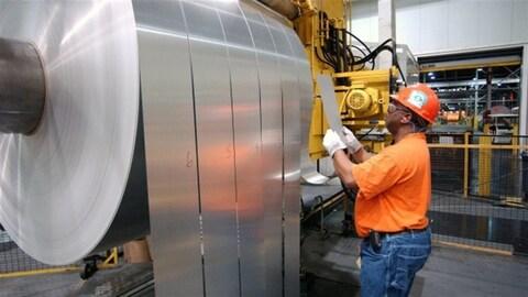 Un travailleur inspecte une feuille d'aluminium