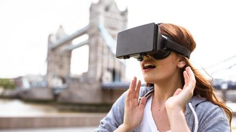 Une femme en train d'utiliser un masque de réalité virtuelle près du Tower Bridge de Londres.