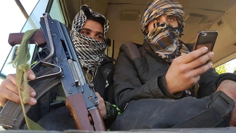 Deux rebelles évacués de la Ghouta sont assis côte-à-côte dans un autobus. L'un tient une arme, l'autre, un téléphone cellulaire.
