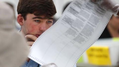 Un homme observe attentivement un bulletin de vote.